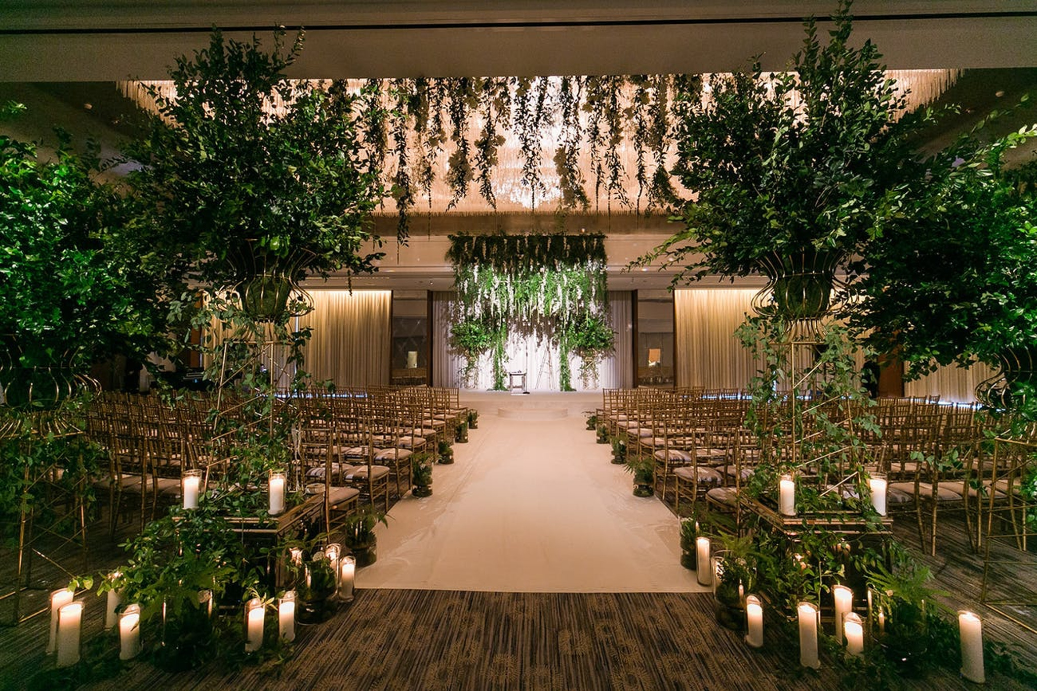 indoor wedding ceremony with greenery and candles lining the aisle at the Ritz Carlton in Chicago