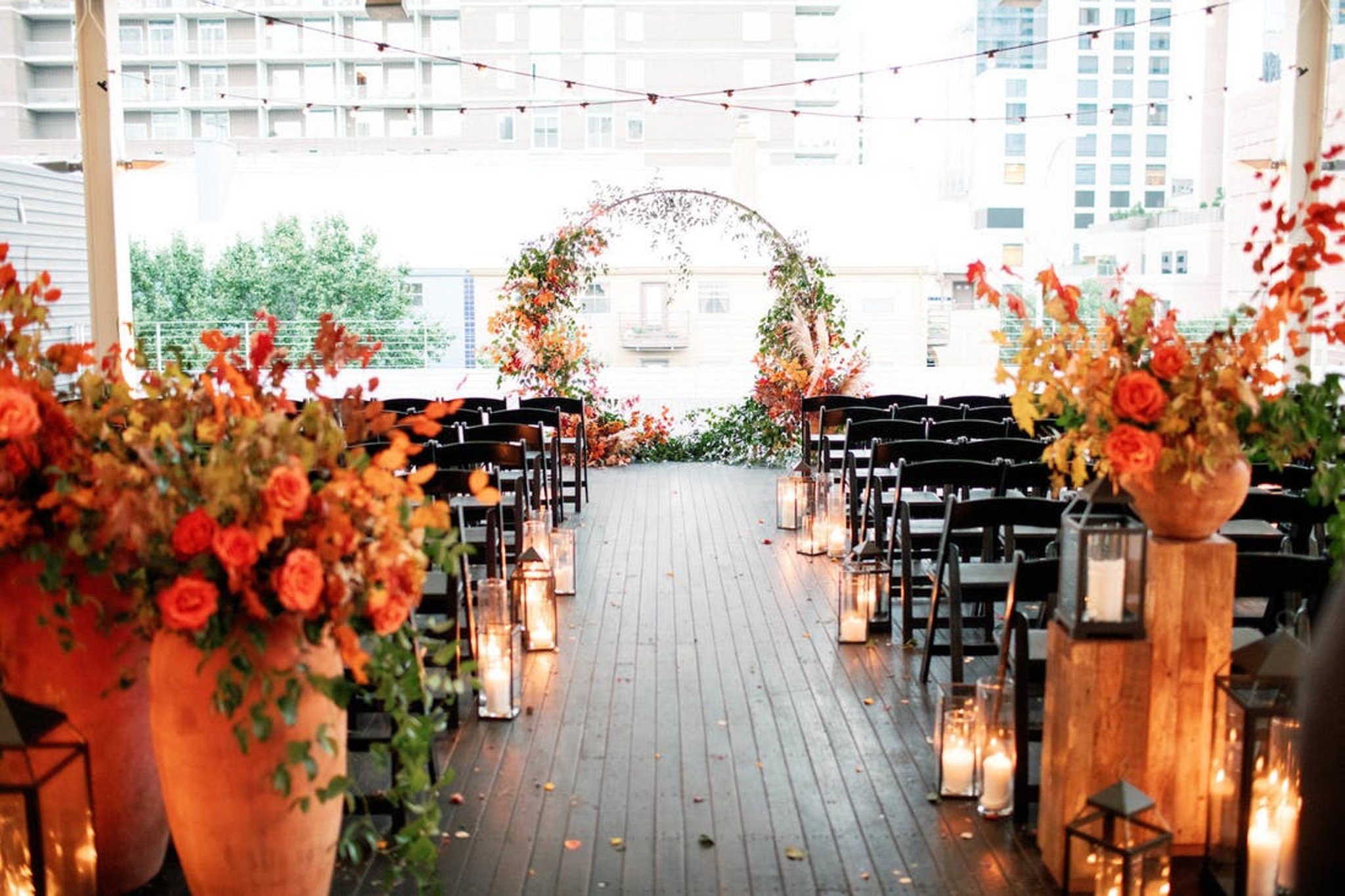 rustic outdoor fall wedding ceremony aisle lined with candles, lanterns orange flowers and a circular floral arch at the end made of orange flowers and greenery