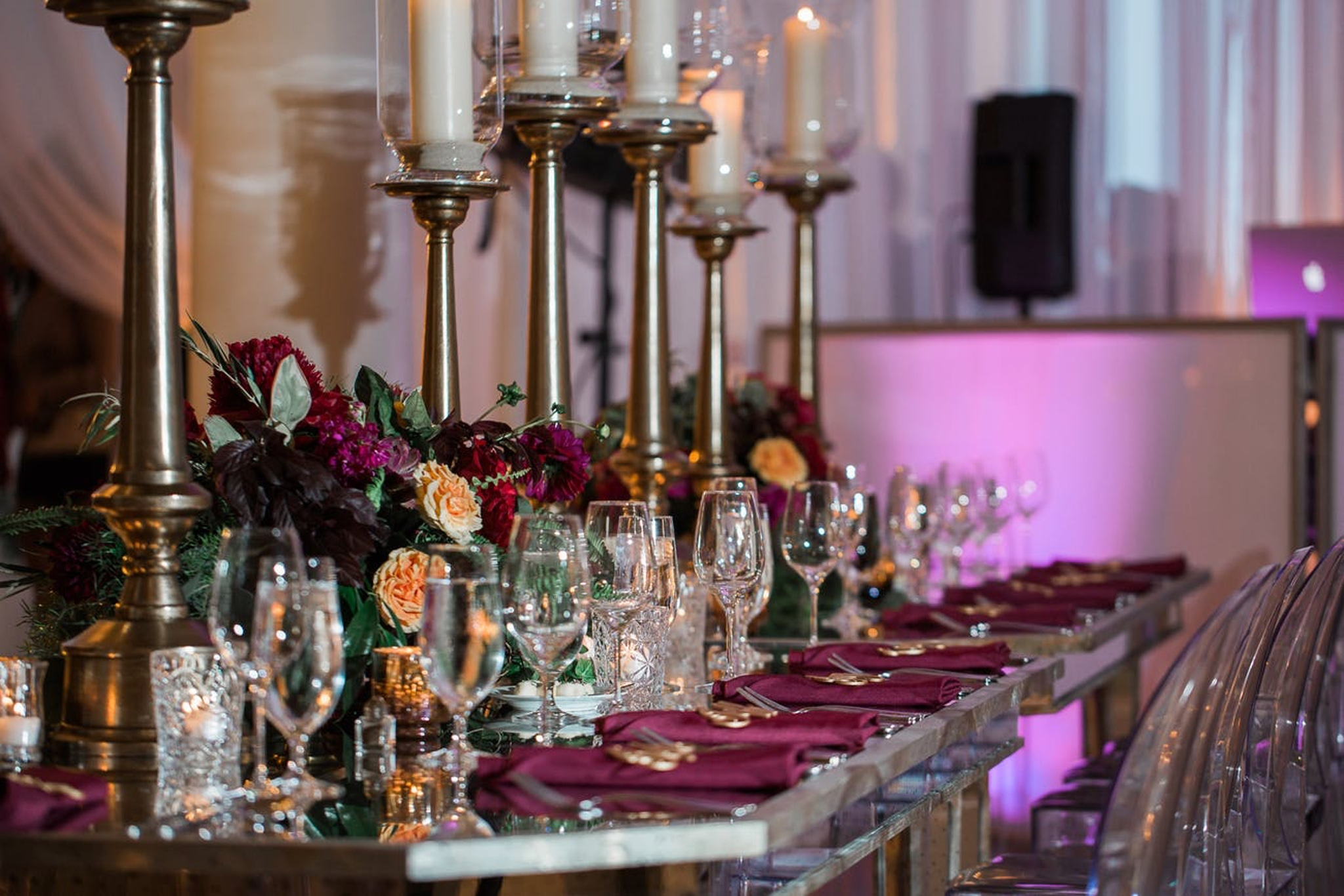 berry colored tablescape at a fall wedding reception with gold candles and pink lighting