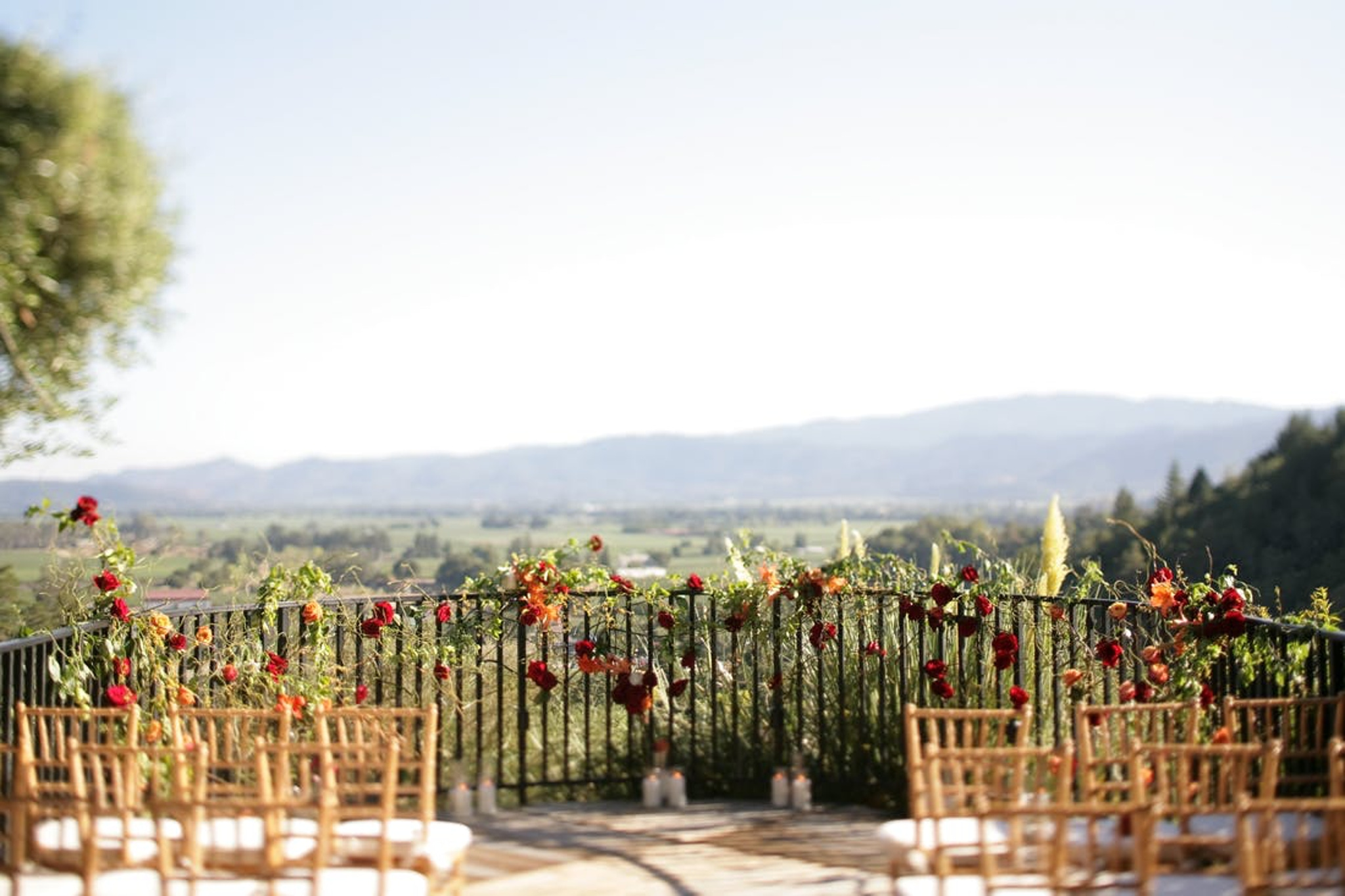 outdoor wedding ceremony in Napa at Auberge du Soleil with red and orange flowers inspired by fall