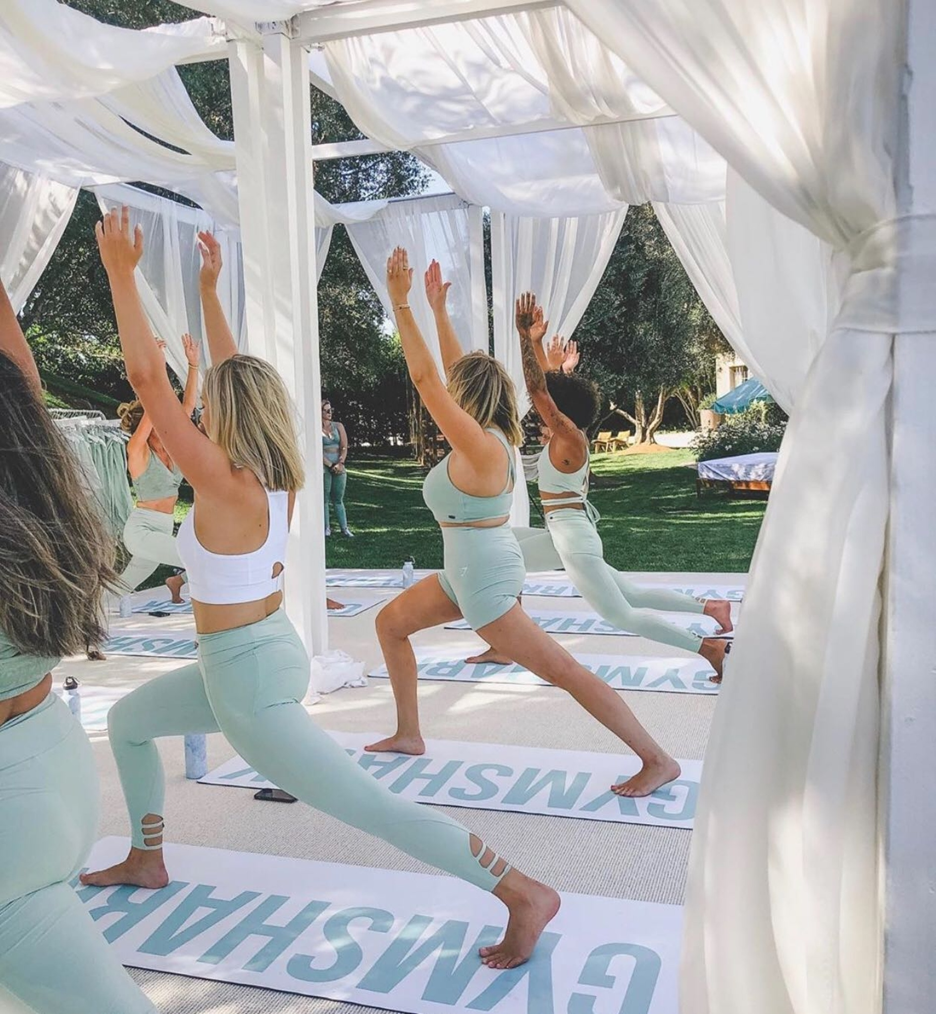 yoga under white cabana at Poosh event in LA