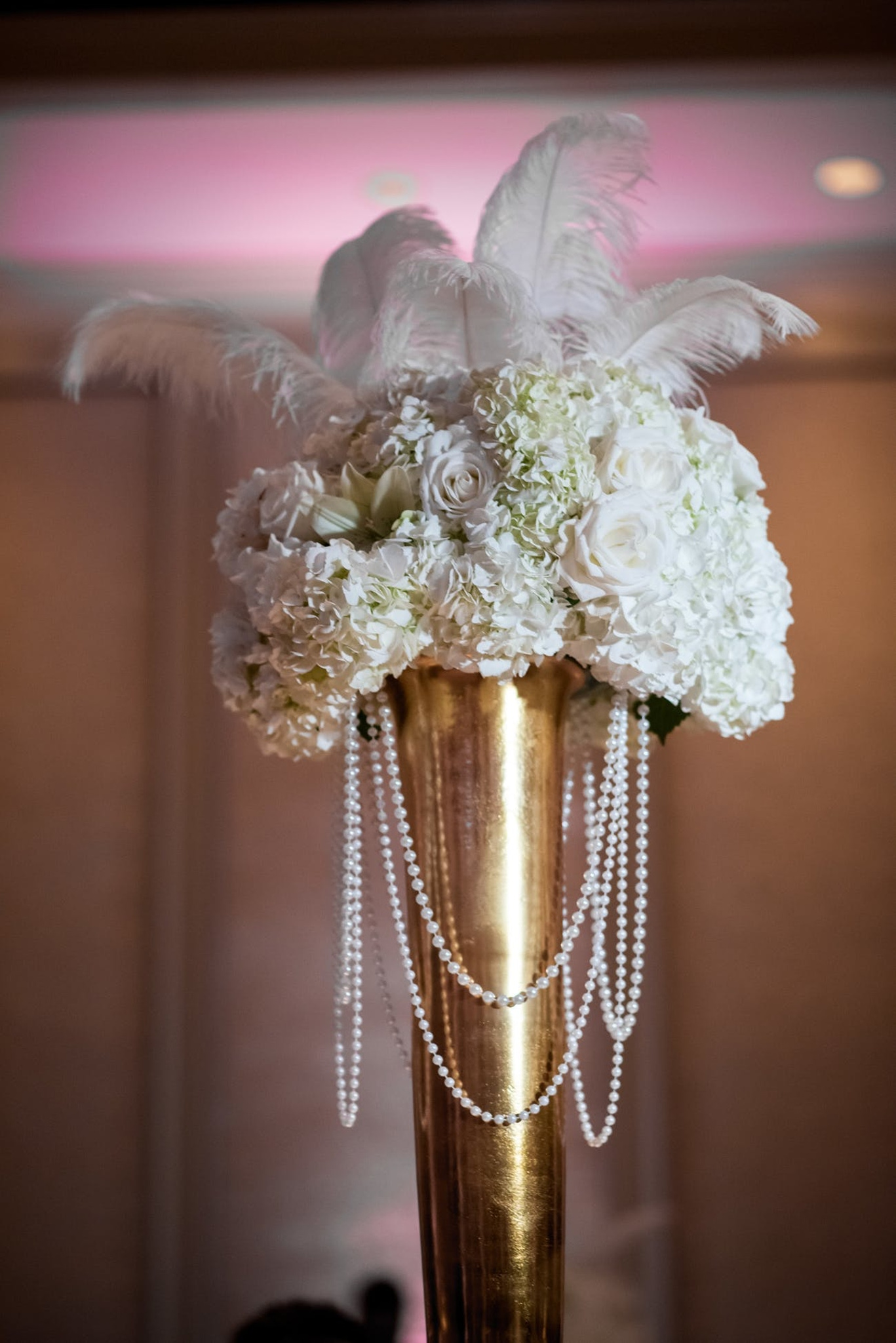 gatsby themed floral centerpiece with feathers and pearls at a new year's eve wedding reception