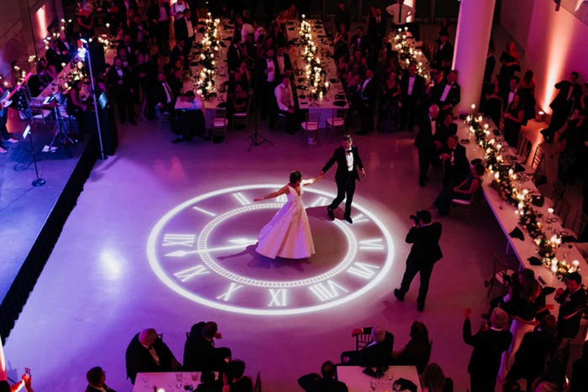 couple dances on a projected clock on the dance floor
