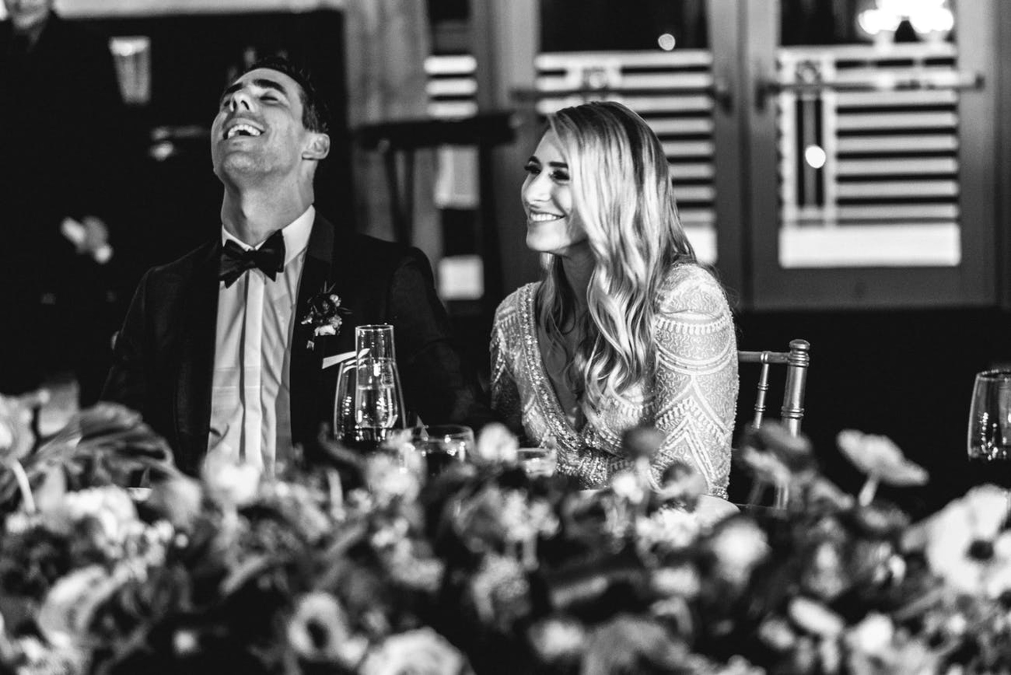 bride and groom at a palm beach wedding reception laughing at the head table