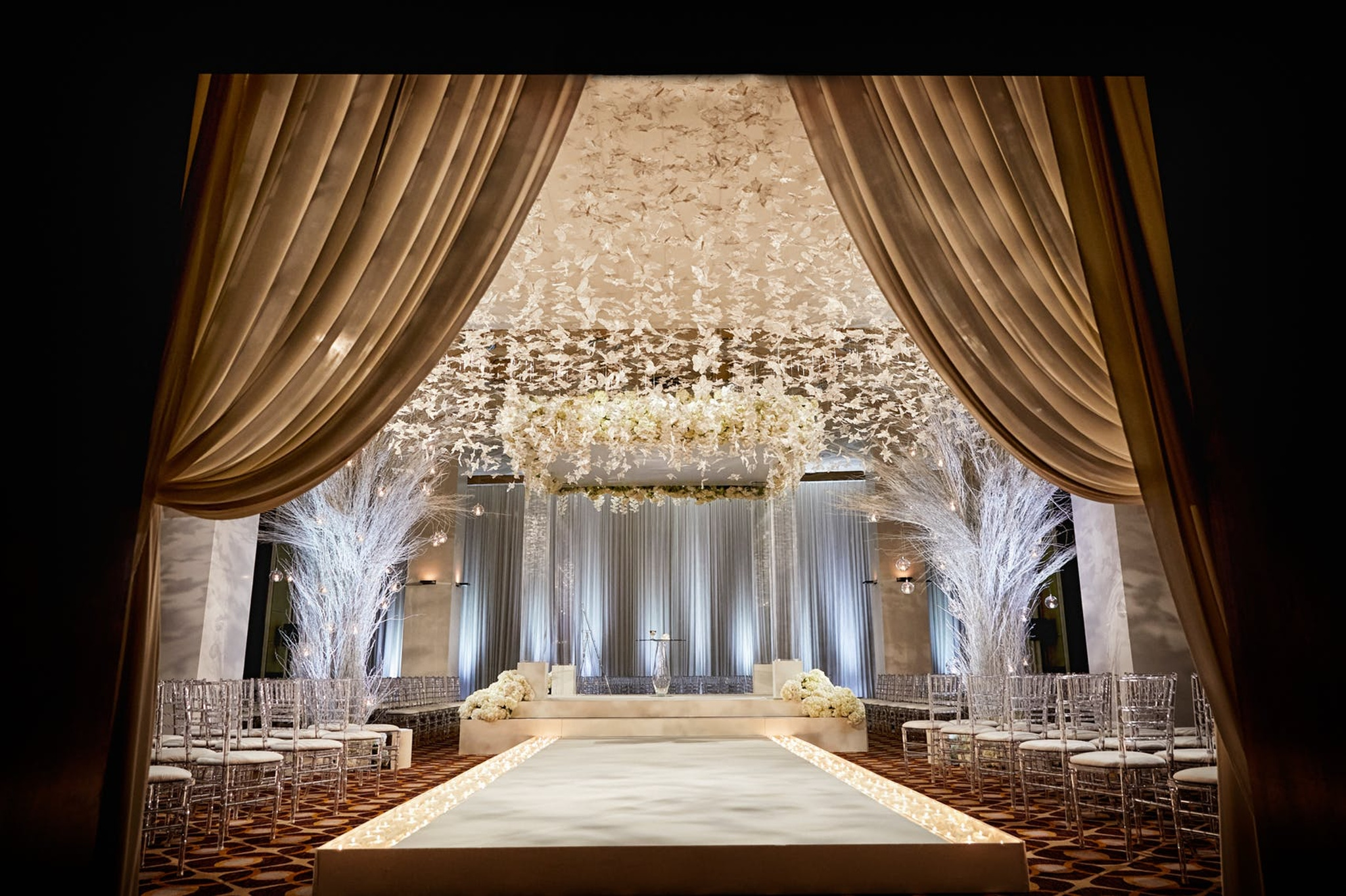 white paper cut butterflies hanging over wedding ceremony