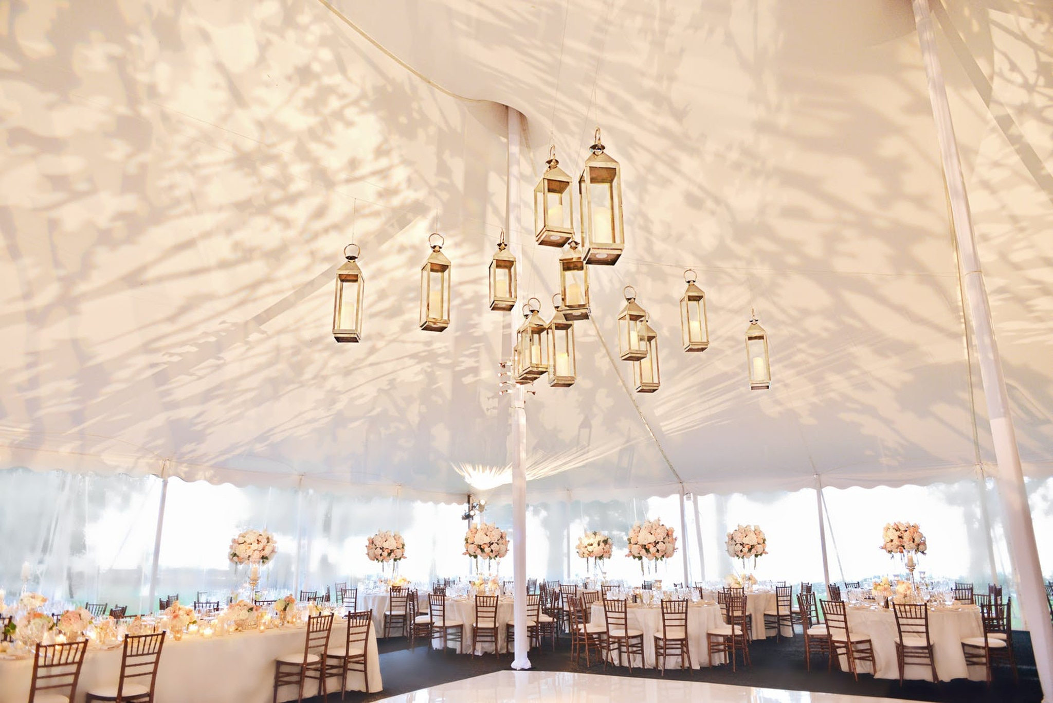 candlelit lanterns hanging in a white tent