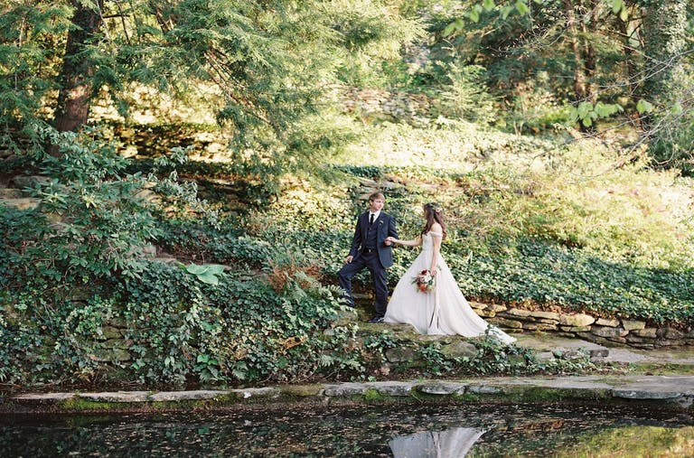 Bride and groom walking through lush greenery