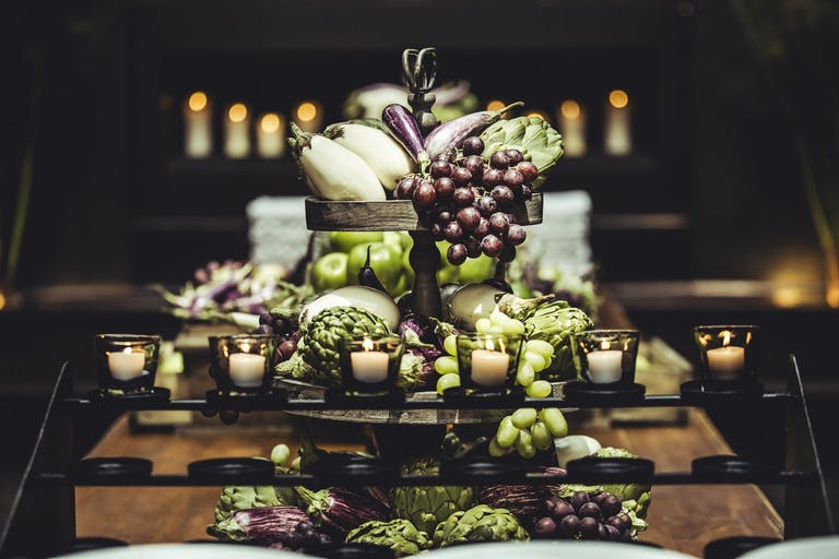 Wedding centerpiece of grapes, apples, and eggplants | PartySlate