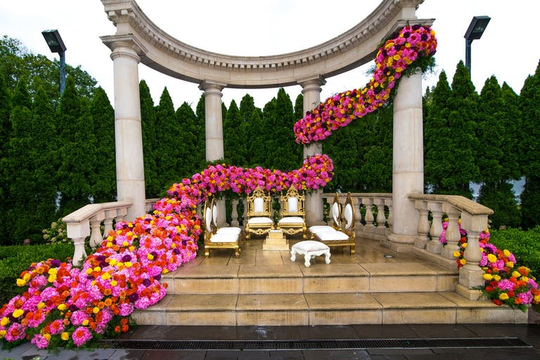 Wedding alter with pillars decked in cascading pink blooms | PartySlate