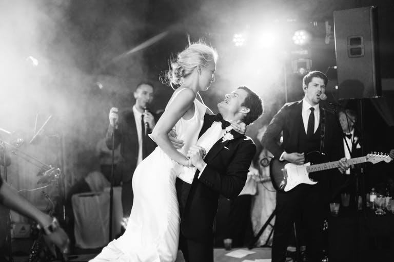 Black-and-white photo of groom lifting up bride in front of band