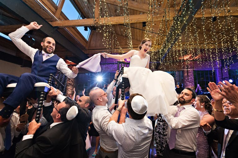 Bride and groom lifted up on chairs during horah