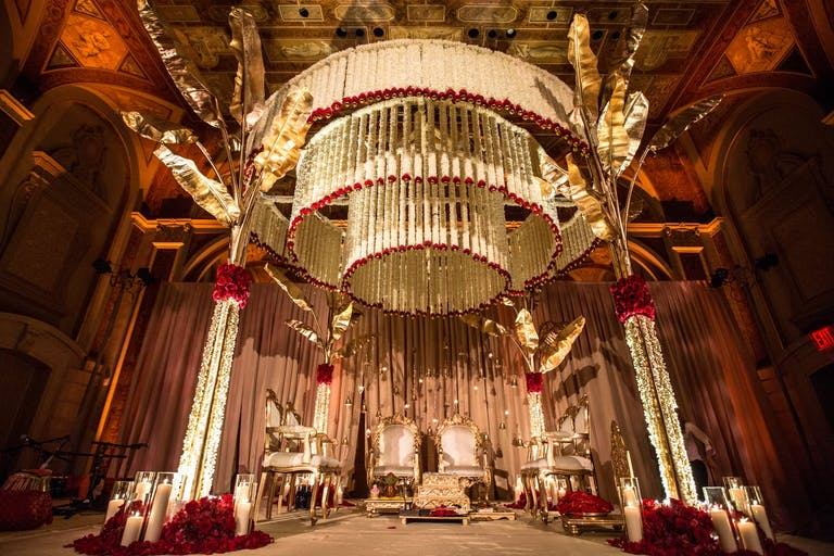 Mandap with concentric circles of suspended white and red blooms | PartySlate