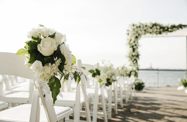 Seaside ceremony with white roses | PartySlate