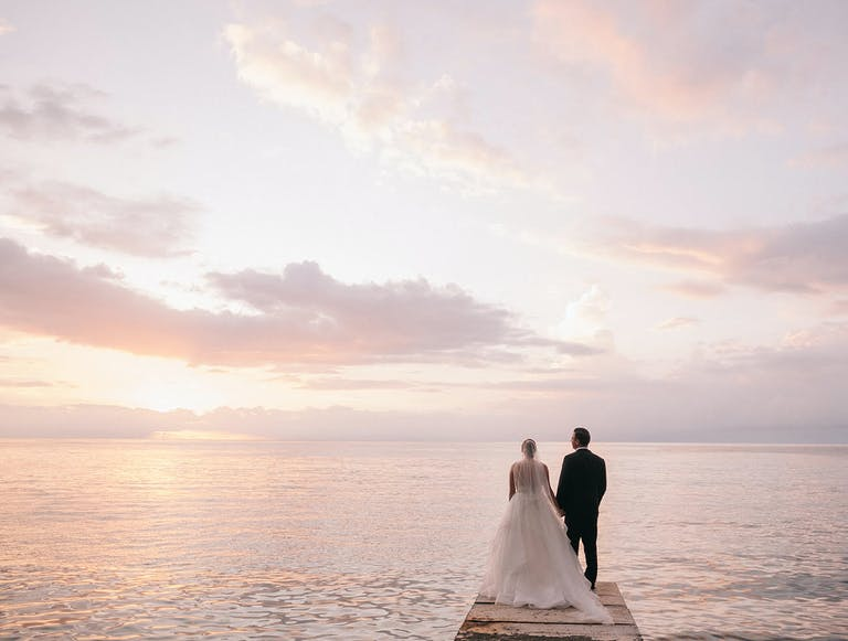 Bride and groom on pier staring sun setting over the water