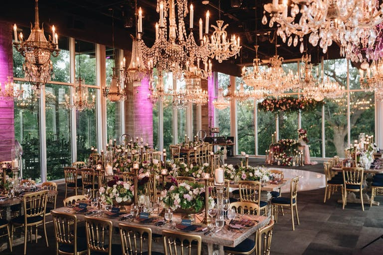 dining room with glittering chandeliers, floor-to-ceiling windows, and pink uplighting