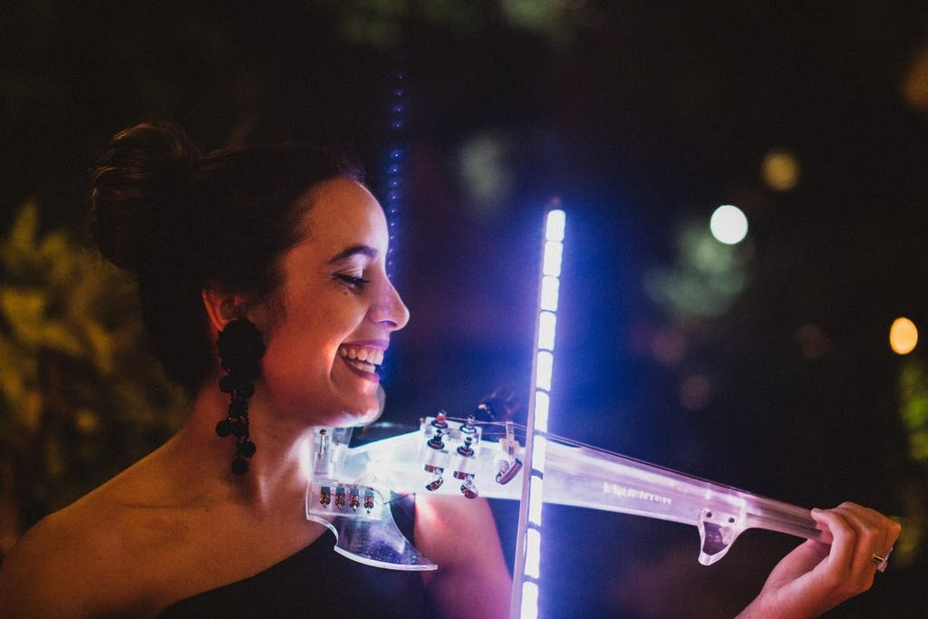Woman playing a neon-lit violin