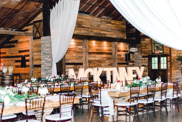 barnyard reception area with white drapery and monogrammed signage