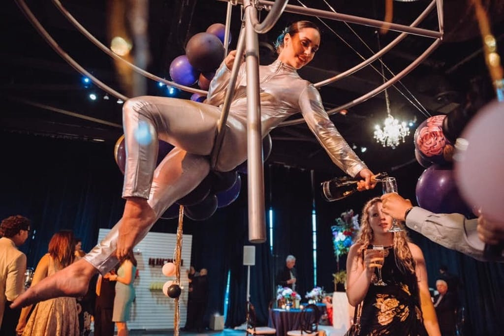 Female aerialist suspended from geometric shape