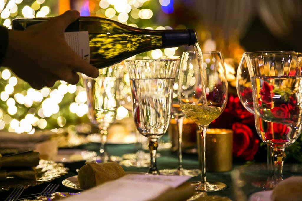 cropped photo of hand pouring a glass of white wine
