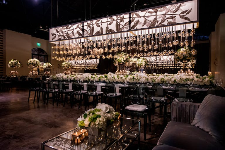 Bar area with suspended candlelit globes and a counter with white floral arrangements