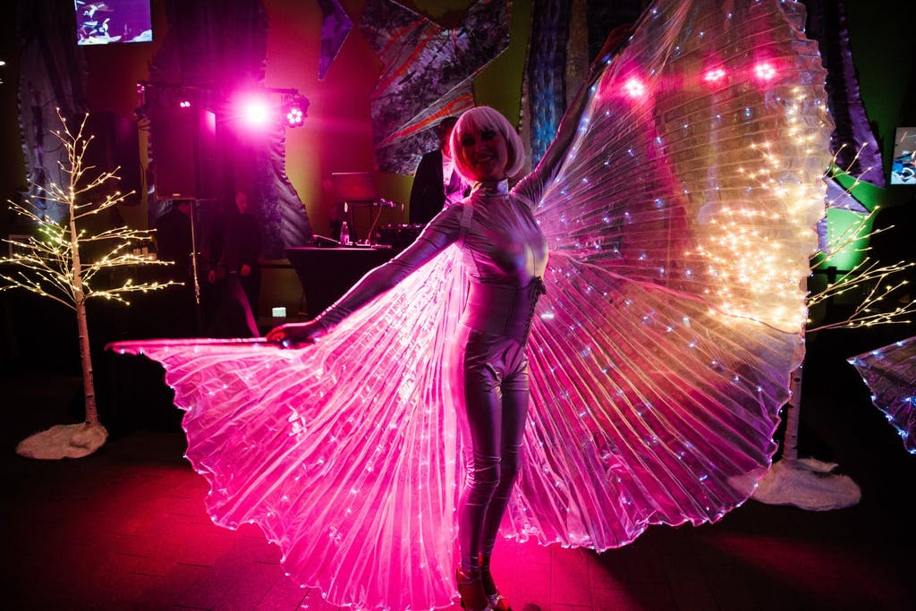 Woman dressed as butterfly with pink up-lit wings