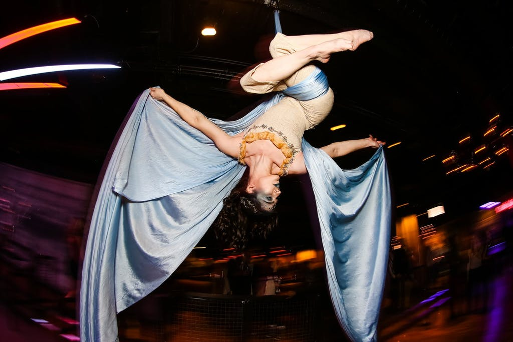 Female aerialist suspended from ceiling