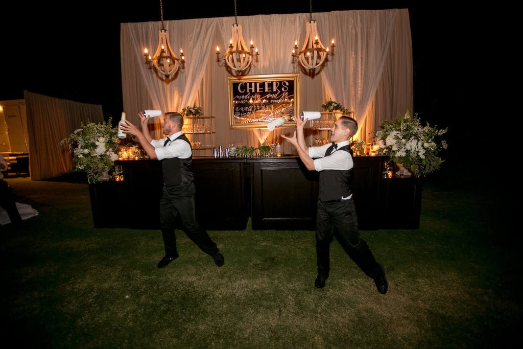 Flair bartenders performing at outdoor wedding