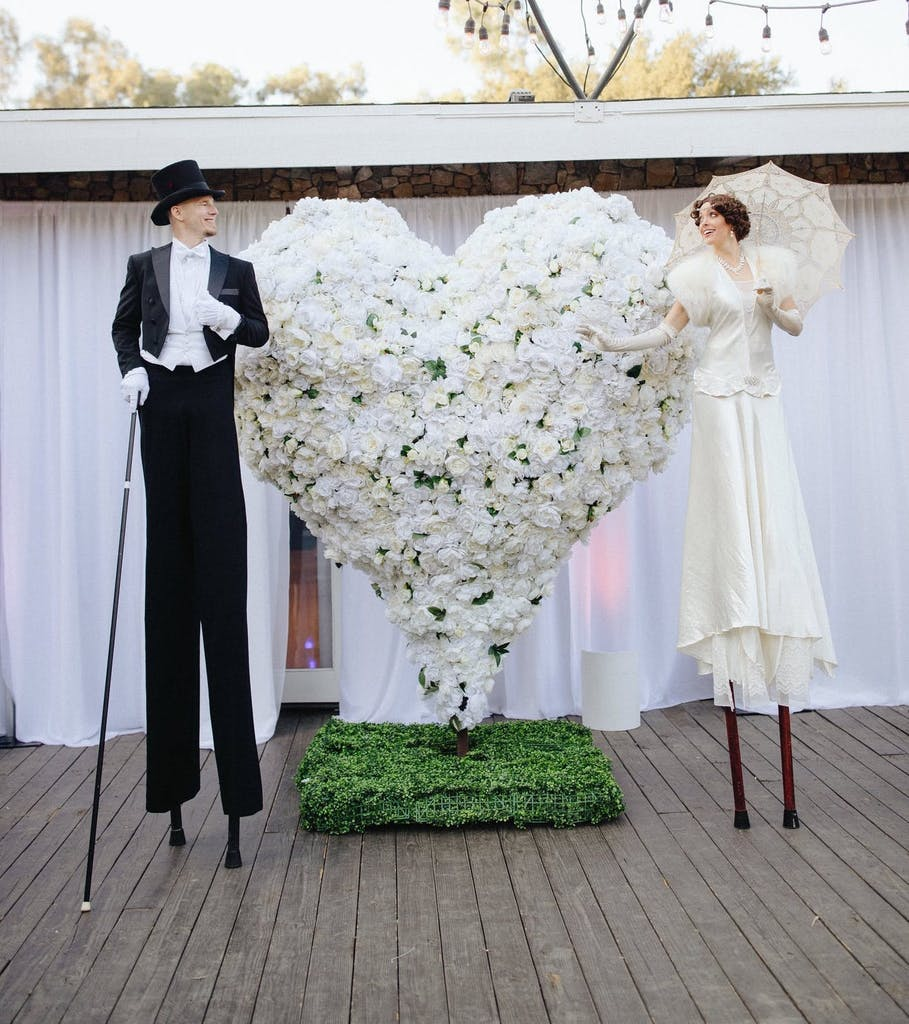 Bride and groom greeters on stilts