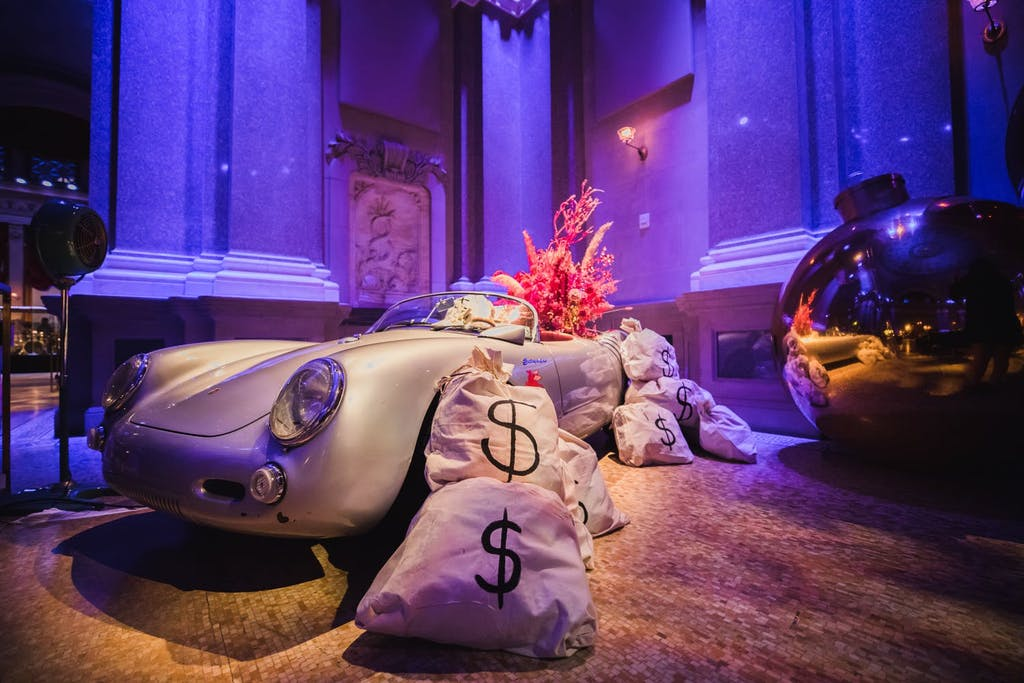 Photo backdrop of vintage car and giant bags of money