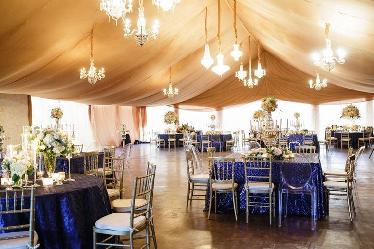 gold-tented pavilion with glittering chandeliers and blue-draped tables