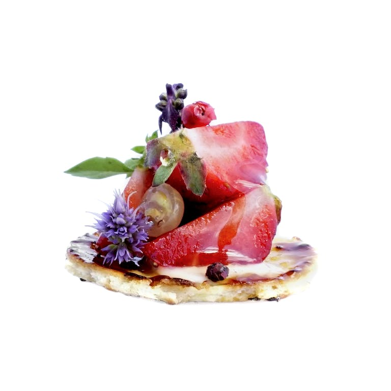 passed bite of strawberry and edible florals on cracker