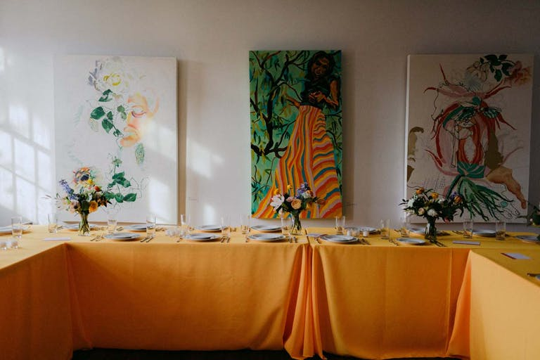 table with orange table cloth and three colorful paintings