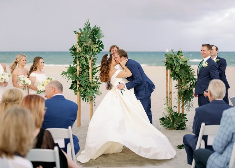 bride and groom kissing at beach ceremony