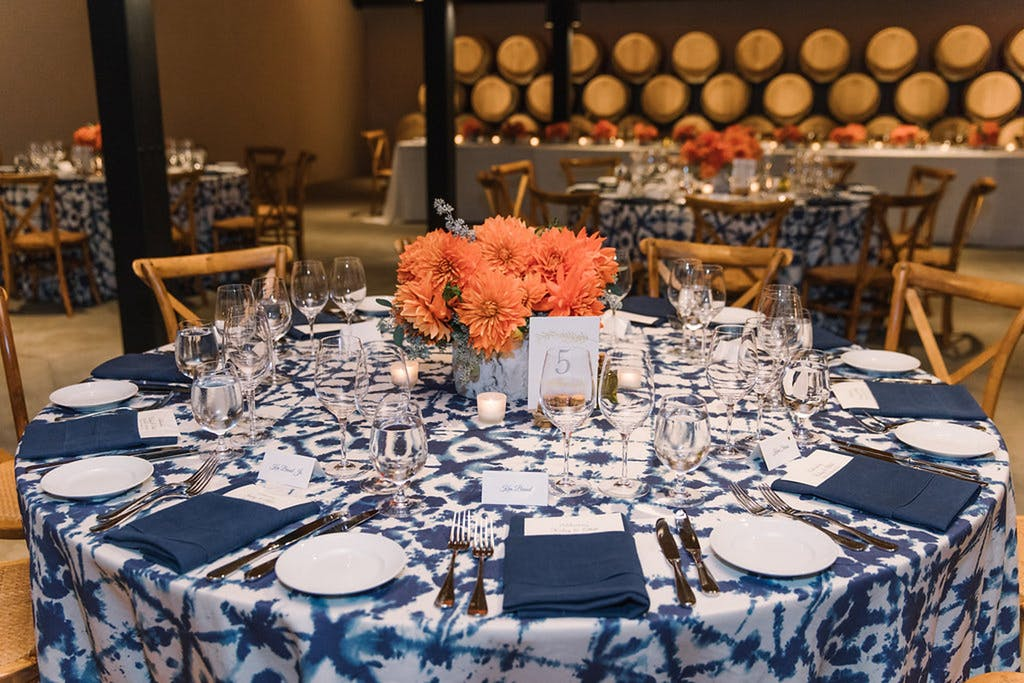 Blue-and-white table cloth with orange floral centerpiece at a wedding rehearsal dinner   PartySlate