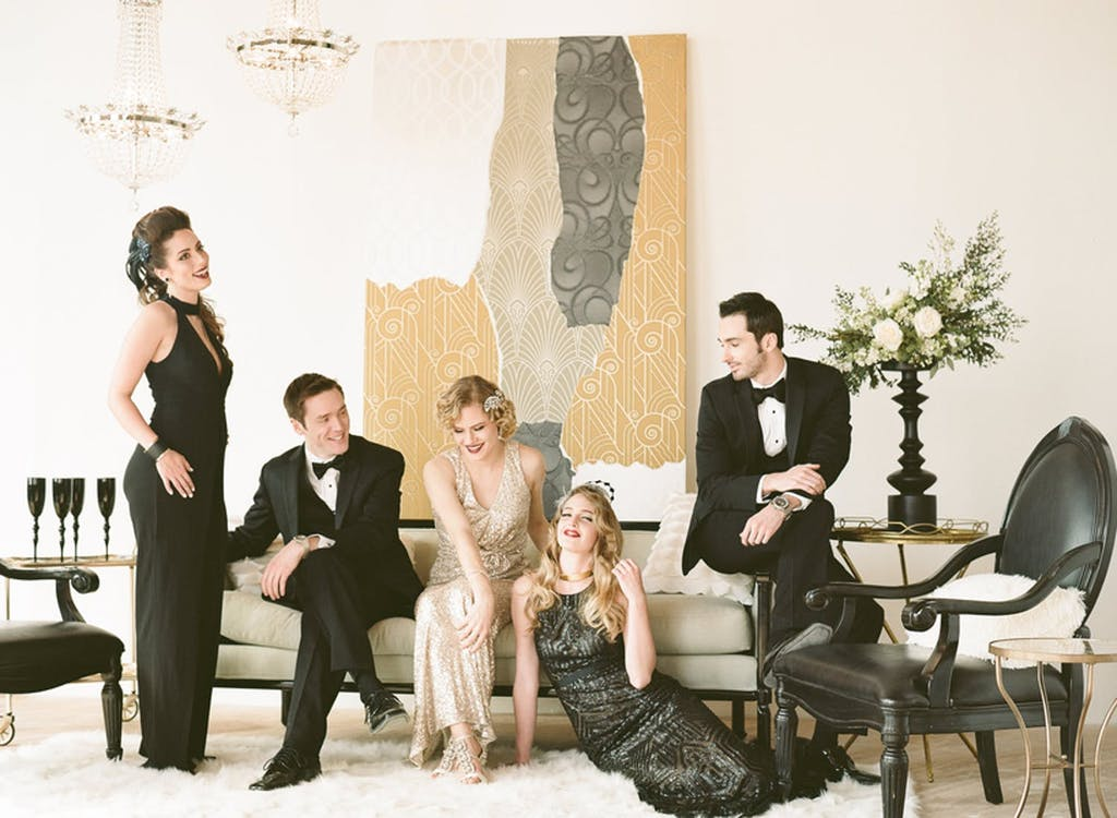 Group of friends lounging in Art Deco costumes at a wedding rehearsal dinner party   PartySlate