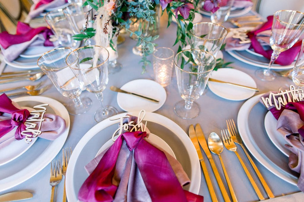 Magenta dinner napkins with each guest's name spelled out in gold lettering at a wedding rehearsal dinner   PartySlate