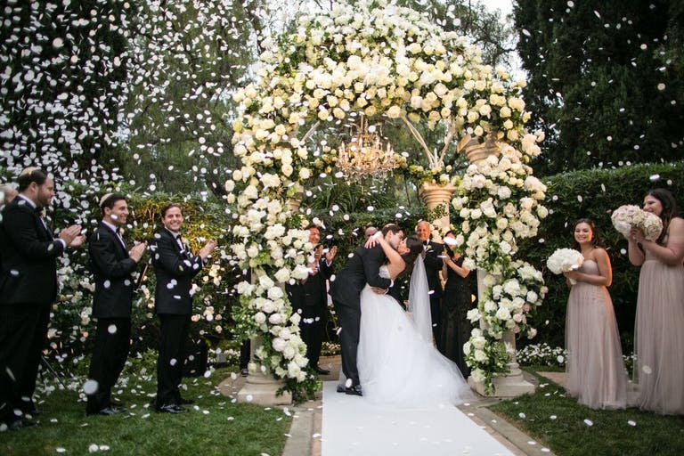 bride and groom kiss during petal toss upon leaving ceremony