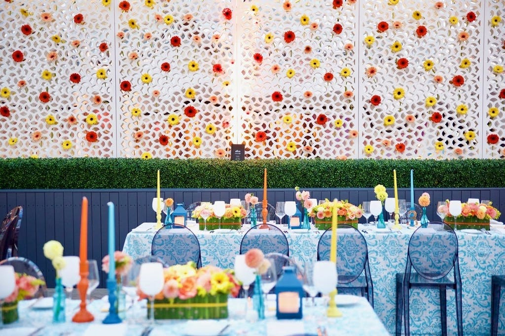 La Sirena dining room with colorful tapered candles and a white wall decorated with red and yellow flowers at a wedding rehearsal dinner party   PartySlate