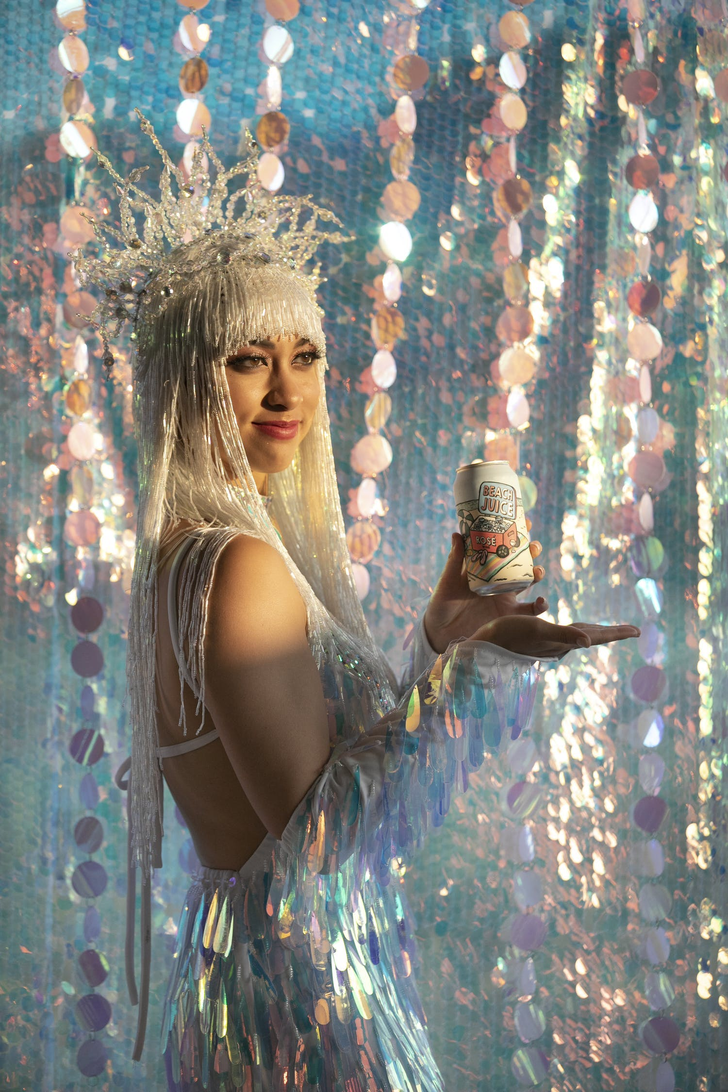 Woman holding beer can against a backdrop of iridescent décor