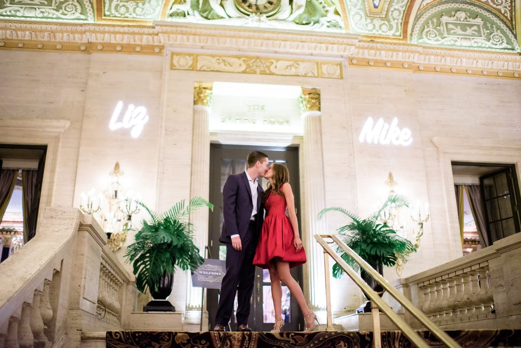 Couple kissing on top of stairway at Palmer House Hilton in Chicago for a wedding rehearsal dinner party   PartySlate
