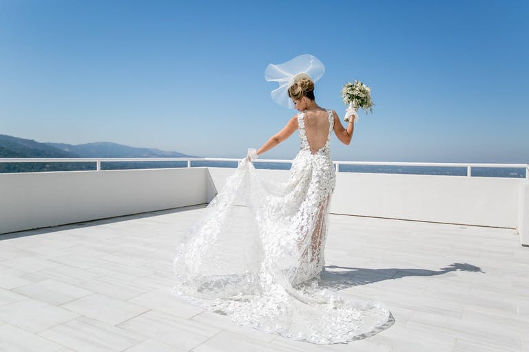 bride posing on white deck surrounded by blue skies