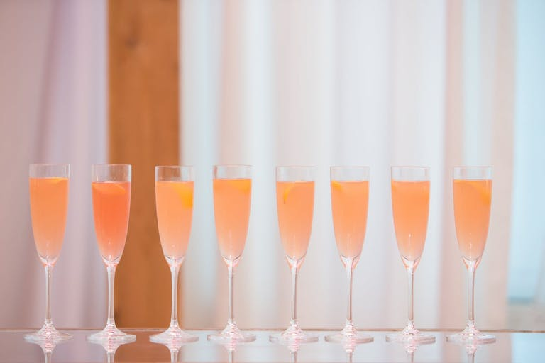 eight champagne glasses filled with rosé.