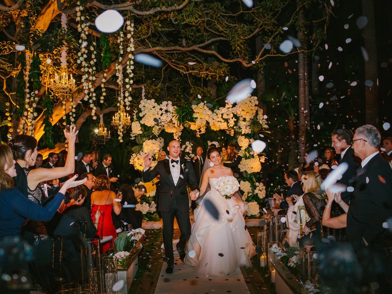 bride and groom exiting wedding during confetti toss