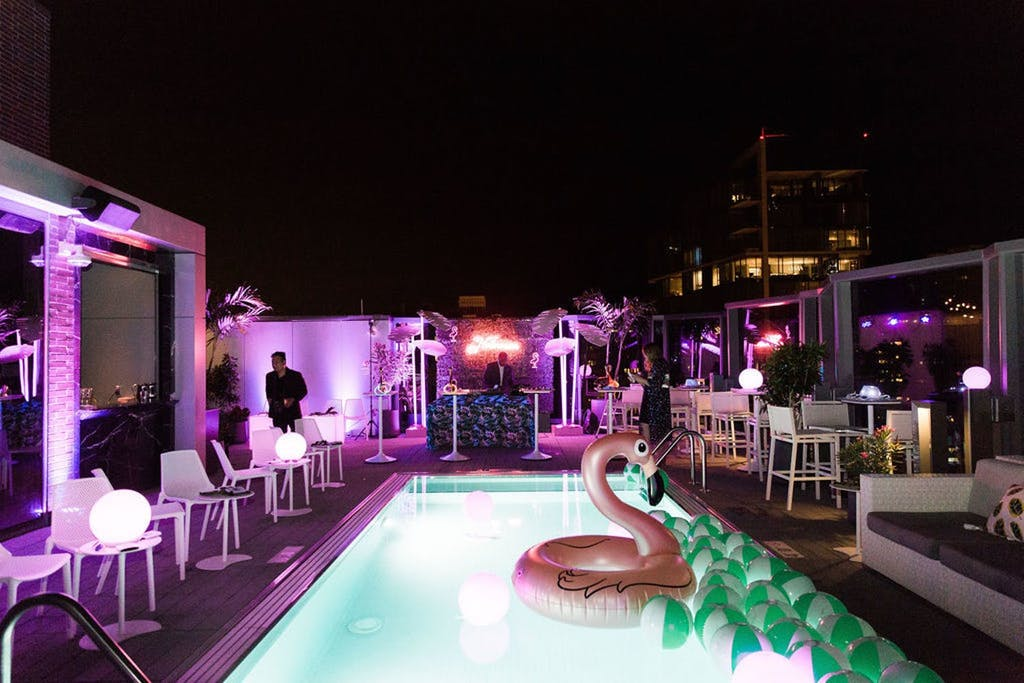 Pool area with flamingo floaty and violet uplighting