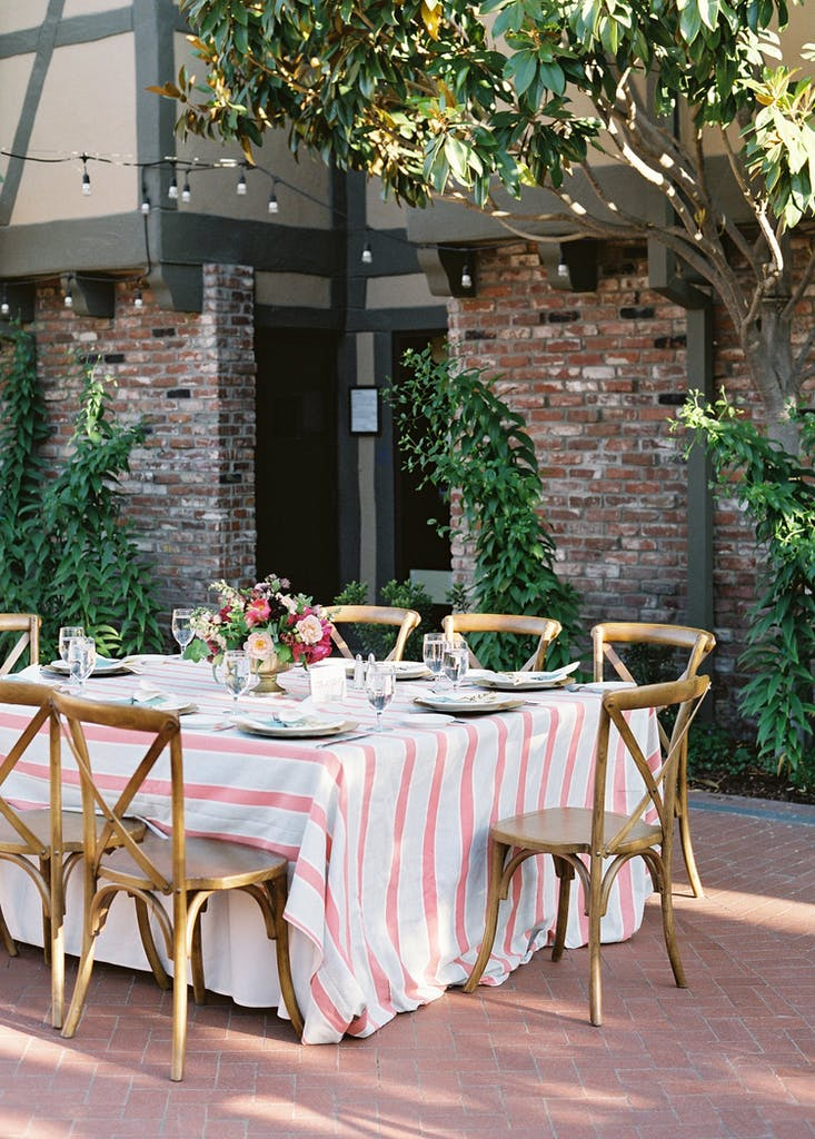 Banquet table with pink-and-white stripped tablecloth in courtyard at a wedding rehearsal dinner   PartySlate