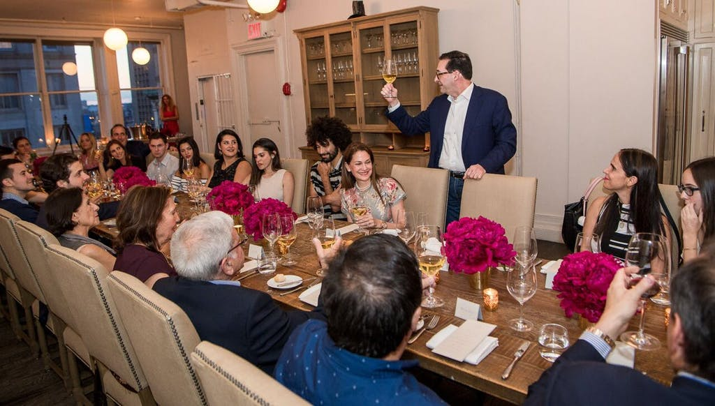 Man raises toast to banquet table full of guests at a wedding rehearsal dinner   PartySlate