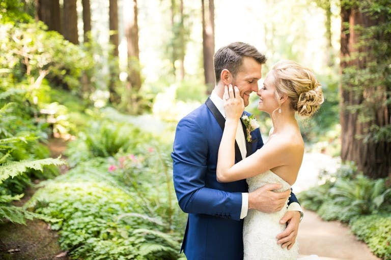bride and groom about to kiss against forest backdrop