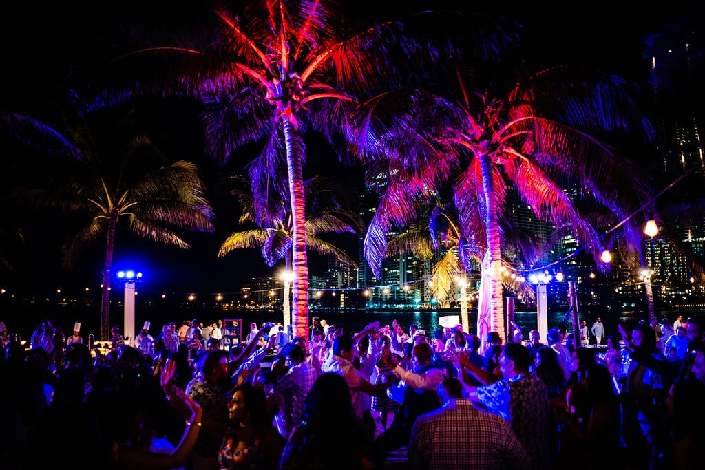 Outdoor wedding rehearsal dinner with colorful uplighting in palm trees