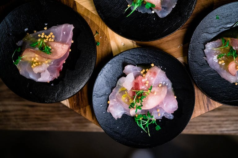 pink Poke fish served on black plates