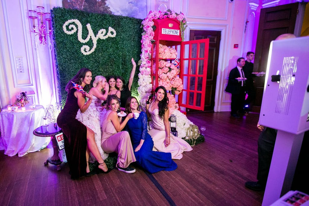 """Guests posing in front of boxwood backdrop with """"yes"""" signage"""